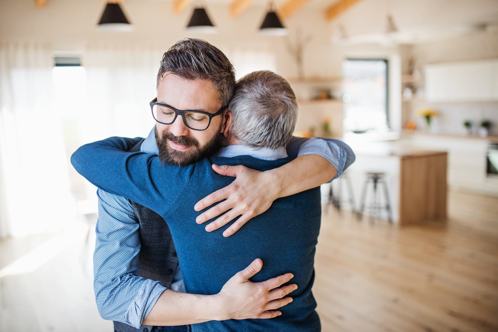 adult son and elderly father hug
