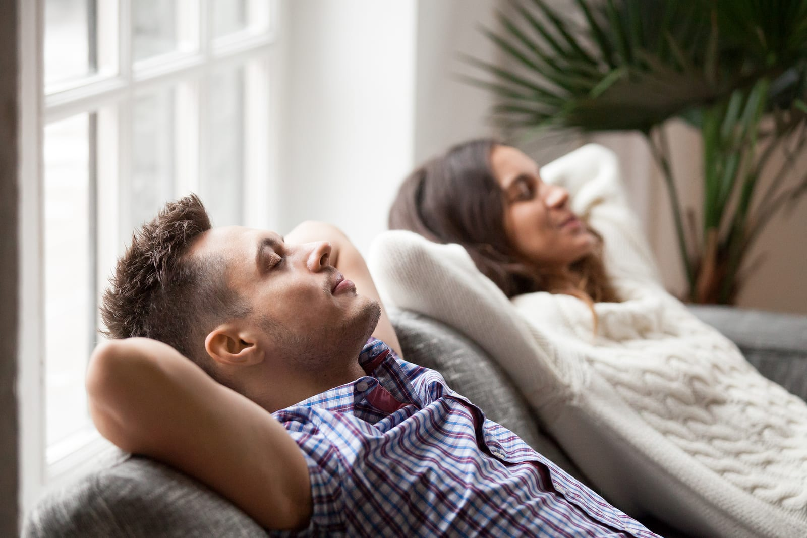 A young couple relaxes at home on the couch while deep breathing to reduce stress and anxiety.